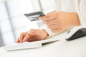 mãos de uma mulher de escritório digitando teclado com cartão de crédito foto