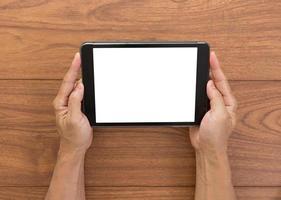 mãos de homem segurando um computador tablet de tela em branco com madeira backgro foto