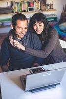 casal apaixonado usando o notebook em casa foto