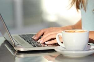 mãos de mulher digitando em um laptop em uma cafeteria foto