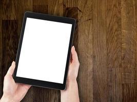 mão de uma mulher segurando um tablet na mesa de madeira de fundo