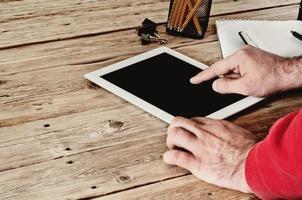 mão masculina clica em um computador tablet de tela em branco foto
