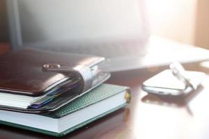 mesa de escritório com um computador e um diário de telefone foto