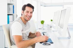 casual homem trabalhando na mesa com computador e digitalizador foto