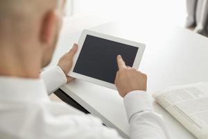 homem de negócios usando o computador digital na mesa no escritório em casa foto