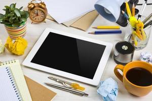 computador tablet em uma bagunça de trabalho na mesa de escritório foto