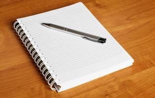 notebokok e caneta na mesa foto