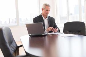 empresário tocando telefone inteligente na mesa foto