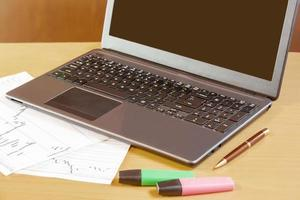laptop, caneta e marcadores na mesa de escritório foto