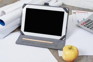 tablet digital com maçã em cima da mesa foto