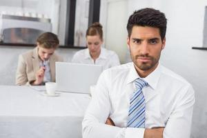 empresário confiante com colegas na mesa de escritório foto