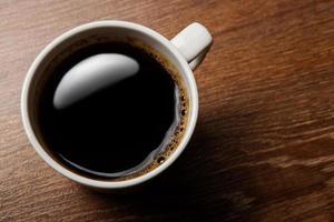 xícara de café preto em cima da mesa