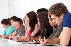 linha de estudantes universitários, escrevendo na mesa foto