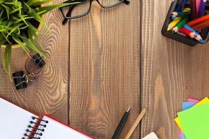 mesa de escritório com flor, bloco de notas em branco e suprimentos