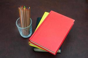 lápis de cor e pilha de livros na área de trabalho de madeira foto