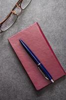 caderno, lápis e óculos foto