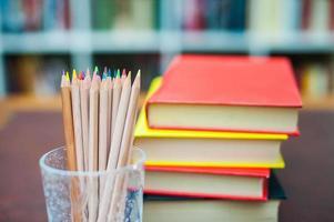 lápis de cor com pilha de livros em segundo plano foto