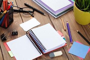 mesa de escritório com o bloco de notas em branco e suprimentos foto