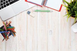mesa de escritório de madeira com planta, laptop, borracha e lápis