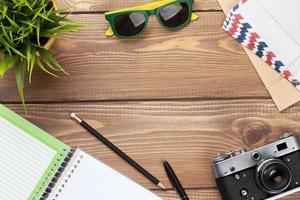 câmera, óculos de sol e suprimentos na mesa de escritório foto