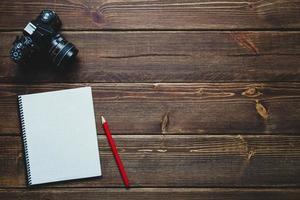 caderno e câmera vintage em cima da mesa foto
