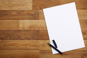 folha de papel e caneta na mesa de madeira foto
