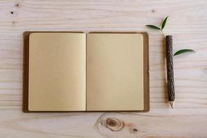 reciclar notebook com lápis de madeira na mesa de madeira foto