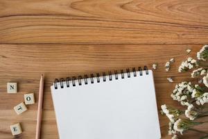 caderno com lápis em uma mesa de madeira foto