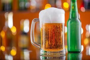 garrafa de cerveja com copo na mesa de bar