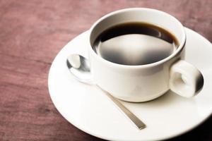 café preto na mesa de madeira foto