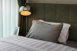 lâmpada de mesa de metal e travesseiro cinza na cama
