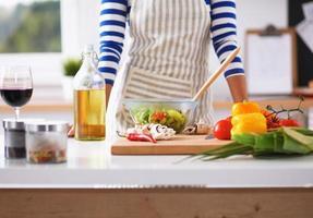 jovem mistura salada fresca, em pé perto da mesa foto