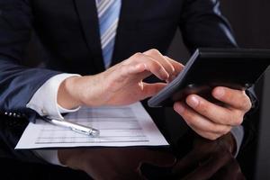 empresário usando calculadora enquanto verifica as despesas na mesa foto