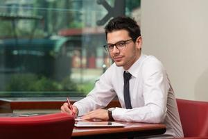 empresário sentado na mesa do escritório, assinando um contrato foto