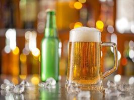 garrafa de cerveja com copo na mesa de bar foto