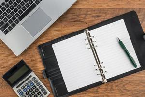 caderno e caneta com calculadora em cima da mesa foto