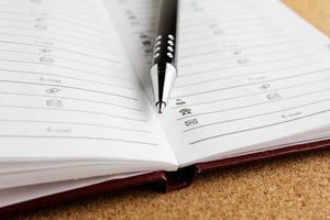 caneta e bloco de notas foto