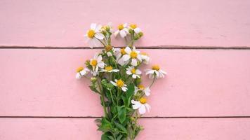 flores em uma mesa de madeira rosa foto