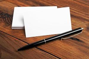 cartões de visita e caneta em uma mesa