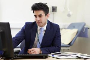 consultor masculino, trabalhando na mesa no escritório foto