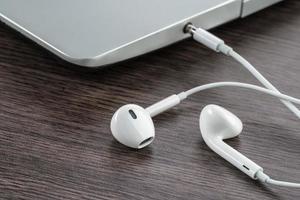 fone de ouvido com o laptop na mesa de madeira