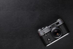 câmera de filme vintage sobre mesa de couro foto