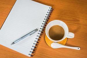 caderno e café em fundo de madeira foto