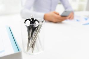 close-up de copo com tesoura e canetas no escritório foto