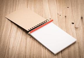 caderno com lápis vermelho na mesa de madeira foto