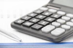 conceito de negócio com calculadora, caneta e caderno foto