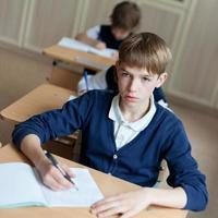 estudante diligente sentado na mesa, sala de aula foto