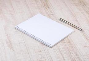 caderno branco em branco em cima da mesa foto