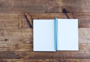 bloco de notas aberto com páginas vazias, deitado sobre uma mesa de madeira foto