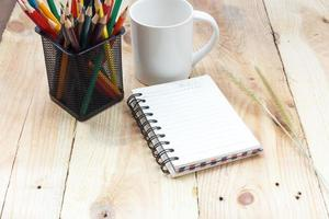 livro de nota de xícara de café e lápis sobre fundo de madeira foto